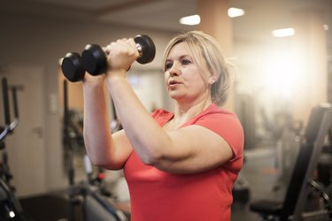 Woman doing upper-body workout at the gym to burn fat