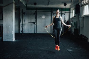 Attractive young woman uses jumping rope to train