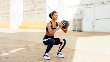 Young Woman With Medicine Ball Exercising On Walkway