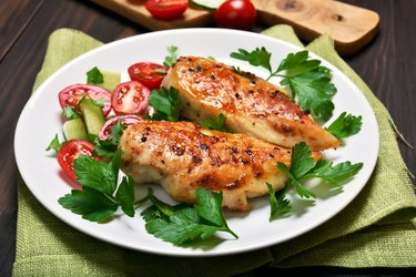 Two pieces of baked chicken breast on a plate with herbs and tomatoes