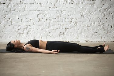 Young yogi attractive woman in Savasana pose, white loft background