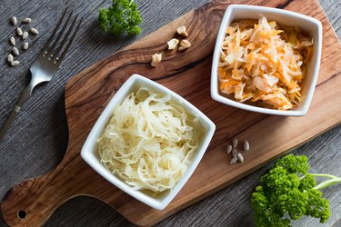 Fermented cabbage and a mix of fermented cabbage with carrots in two square bowls