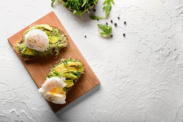 Tasty toasts with avocado and eggs Benedict on wooden board