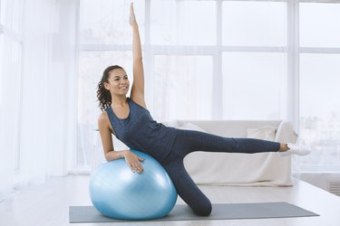 Lovely young lady working out with exercise ball indoors