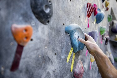 Cropped image of athlete holding rock on climbing wall