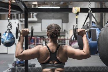 Black woman lifting dumbbells in gymnasium