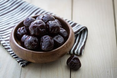 Dried plums in a bowl on wood table