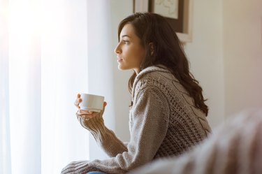 A woman at home drinking green tea or coffee for weight loss