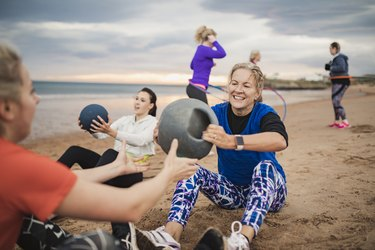 Woman Doing Weighted Ball Exercises During Boot Camp Workout Class