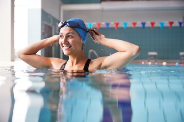 Female Swimmer Wearing Hat And Goggles Training In Swimming Pool