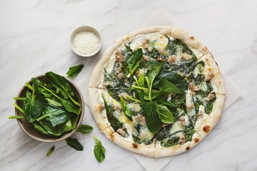 Pizza with chopped meat, spinach and cream sauce