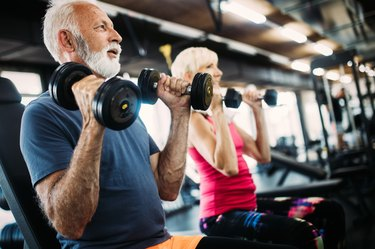 Fit senior sporty couple working out together at gym