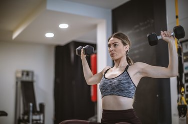 Athletic woman lifting dumbbells in the gym