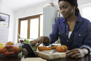 An African-American woman using her tablet to track Weight Watchers points as she cooks dinner