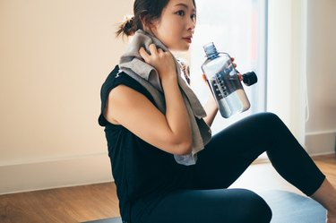 young woman wearing black workout clothes holding water bottle and towel after hot Bikram yoga at home