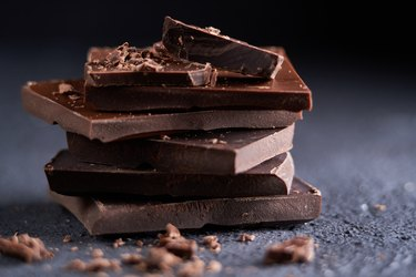 Piece of dark chocolate and chocolate chips on a dark background