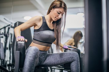 An athletic woman doing leg extensions at the gym