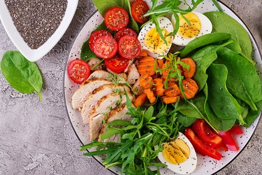 Plate with a keto diet food. Cherry tomatoes, chicken breast, eggs, carrot, salad with arugula  and spinach. Keto lunch. Top view