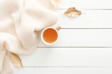 Cozy home desk table with knitted plaid, tea cup, fall leaves on wooden white background. Top view, flat lay, copy space. Autumn composition. Nordic hygge style concept.