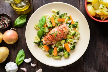 Baked chicken breast wrapped in bacon with veggies
