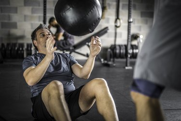 Man doing ab exercises with a medicine ball
