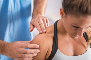 Physical therapy. Therapist addressing trapezius muscle