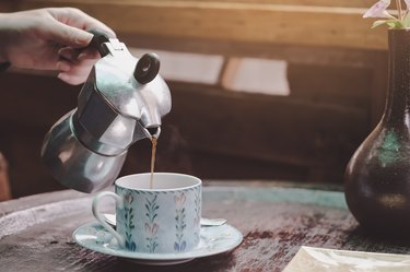 Cropped Hand Of Woman Pouring Tea In Cup