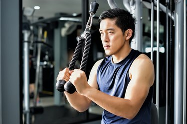 Strong handsome asian man exercising at the gym