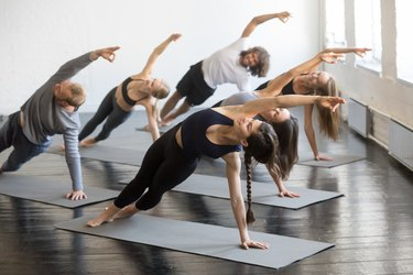 Group of young sporty people in Bending Side Plank pose