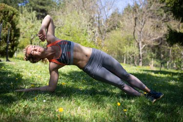 Woman performing 5 hardest ab exercises in her backyard.