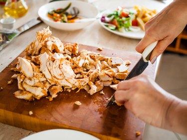 Woman cutting lean chicken breast.