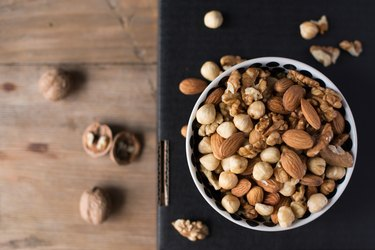 Walnuts, almonds and hazelnuts in a bowl on black background
