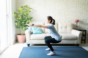 Active woman doing squats at home