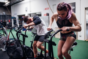 Young woman and man training together on gym exercise bikes, action