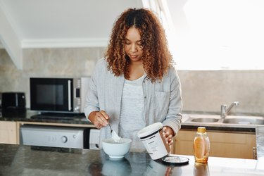 Woman scooping yogurt into bowl in kitchen