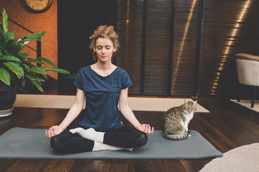 A woman sitting on a yoga mat with her cat and practicing 4-7-8 breathing