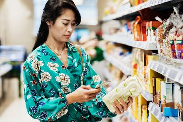 Young Woman Looking Up Food Item Ingredients On Smartphone