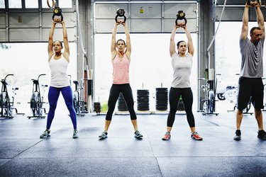 Group of friends training with kettlebells in gym