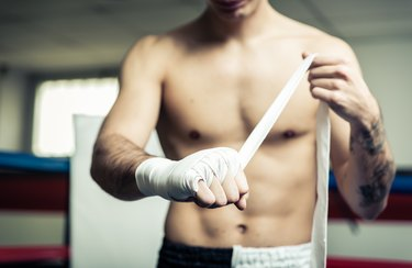 Fighter putting bendage on the hands before training