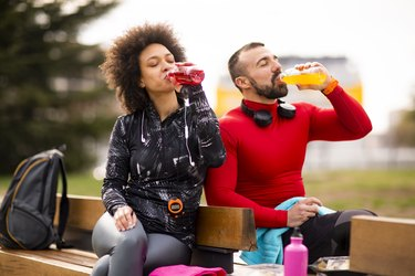 Young couple in sports clothing hydrating themselves while resting together after exercising in a park