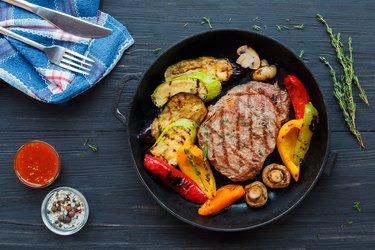 Grilled beef steak on dark wooden table background, top view