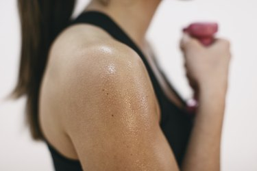 Sweaty shoulder of woman doing fitness workout