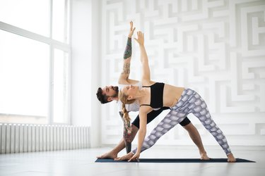Man an woman in a white, new age yoga studio doing triangle pose as part of a yoga flow for digestion