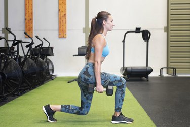 Young athletic woman doing dumbbell lunges to work out her upper leg and buttocks muscles at the gym