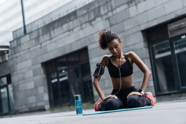 Young fitness woman in earphones sitting relaxed on yoga mat after workout with a water bottle outside