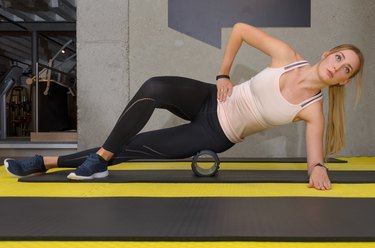 Young blonde woman training with roller at gym