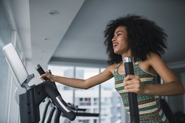 Smiling young woman on step machine in gym