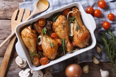 Baked chicken legs with vegetables in baking dish