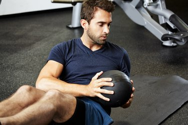 Man using medicine ball to do Russian twist exercise