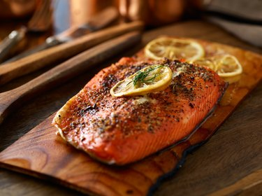 cooked salmon fillet on top of wooden cedar plank